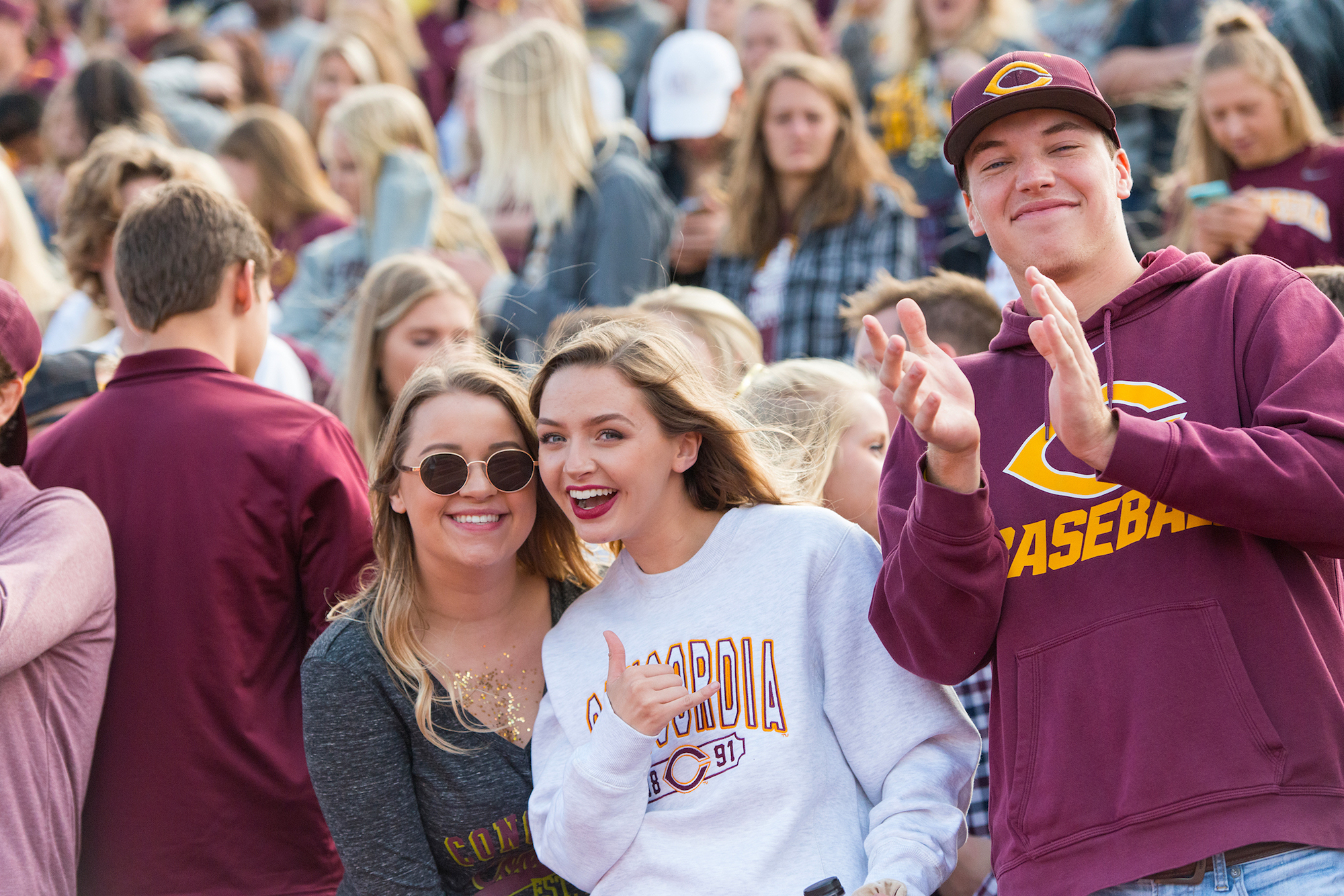 students posing and cheering in homecoming game crowd