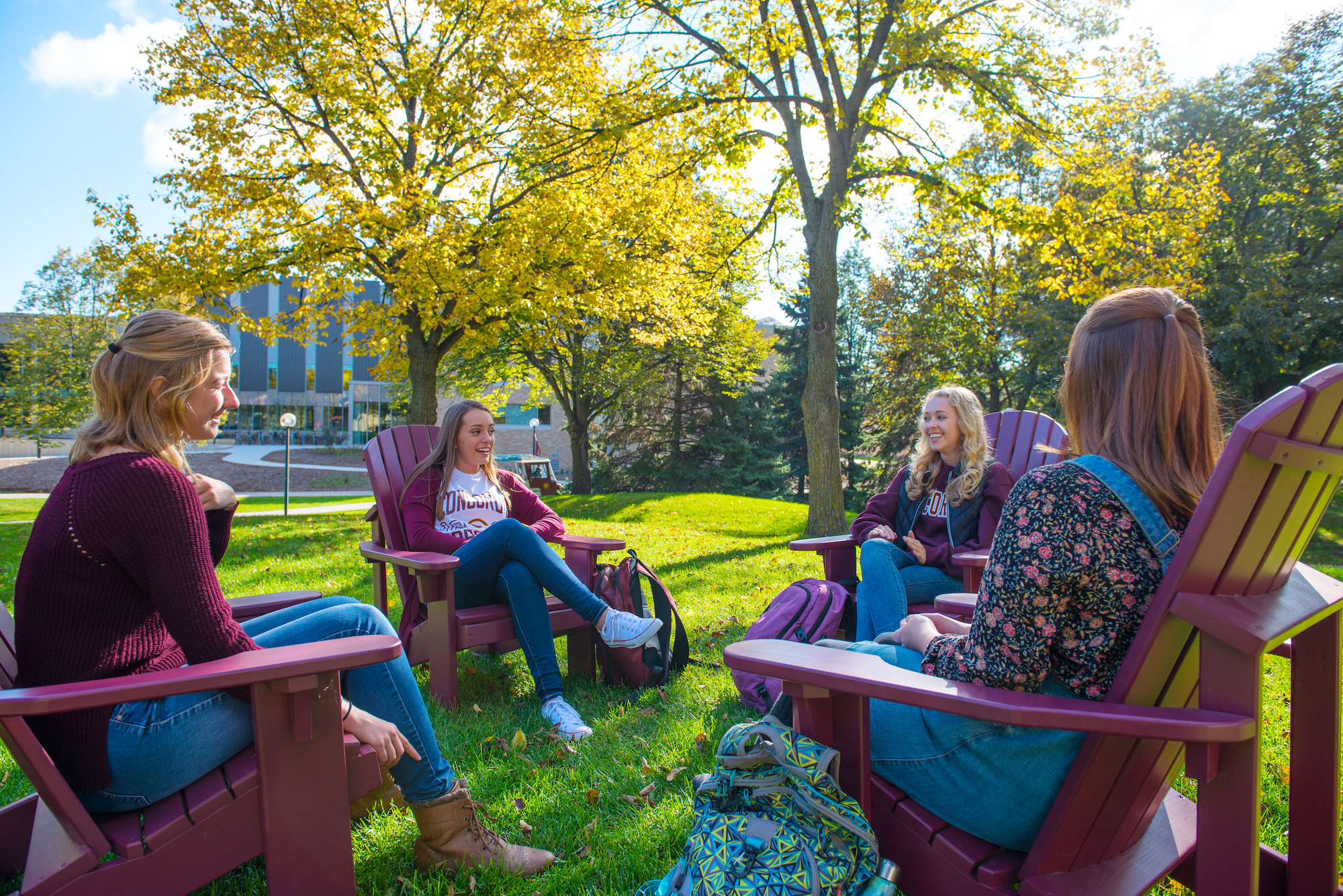 students in adirondack chairs on lawn
