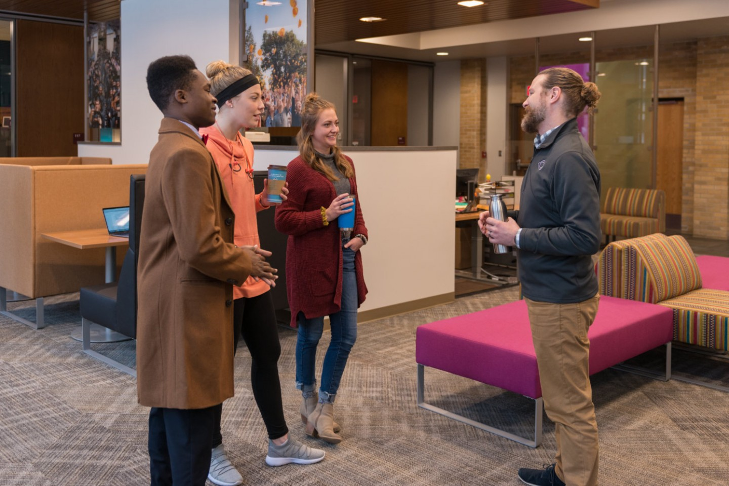 students talking with staff member at student success center