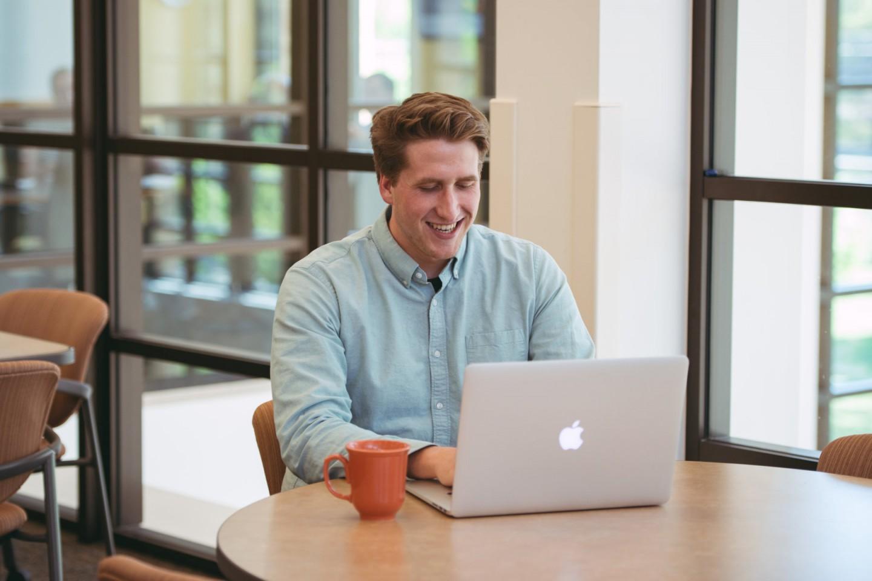 Erik Belz smiling and typing on laptop