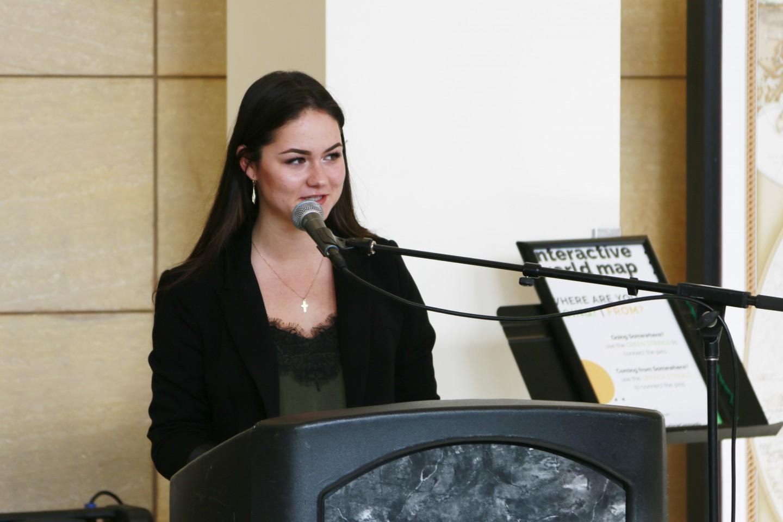 Julia speaking at podium in campus center