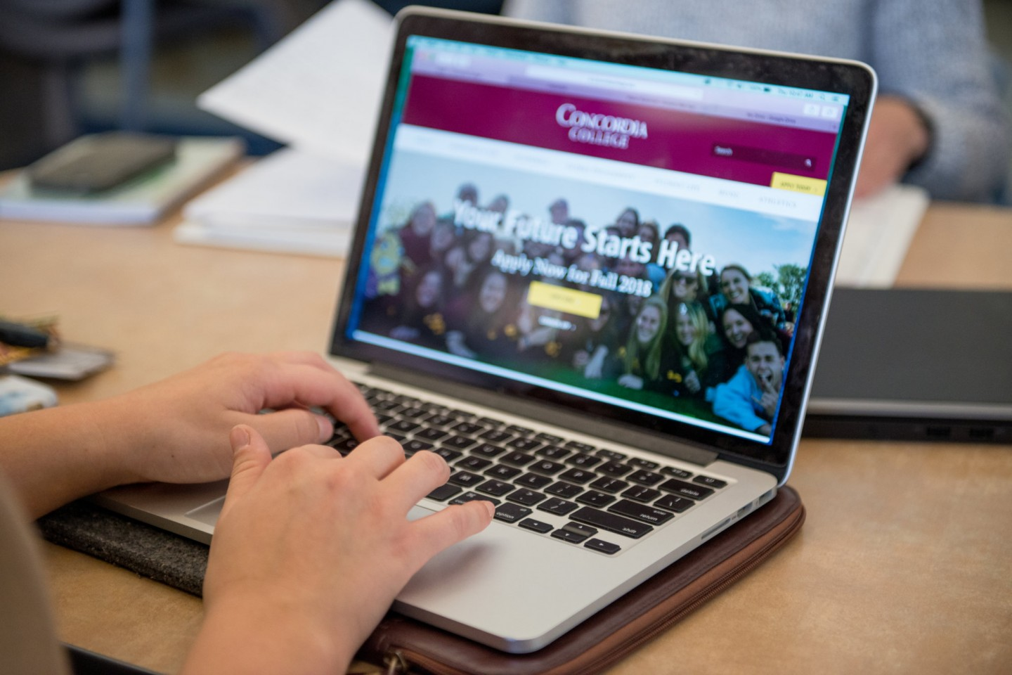 Close up of hands typing on laptop with Concordia website open