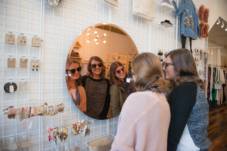 Girls wearing sunglasses looking in mirror