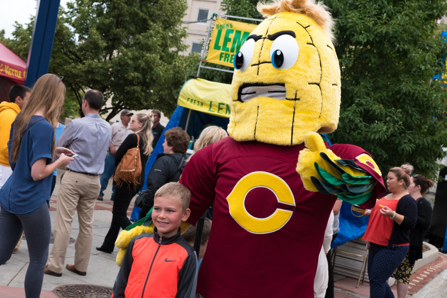 Kernel posing with boy at Street Fair