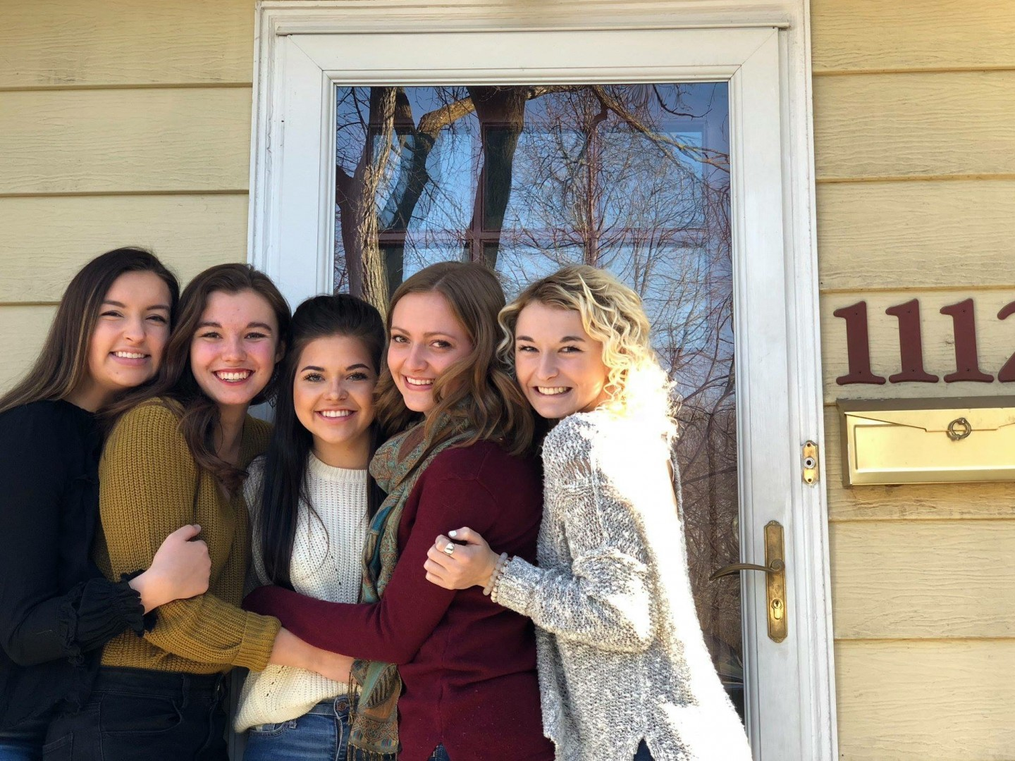 female students on stoop in front of house
