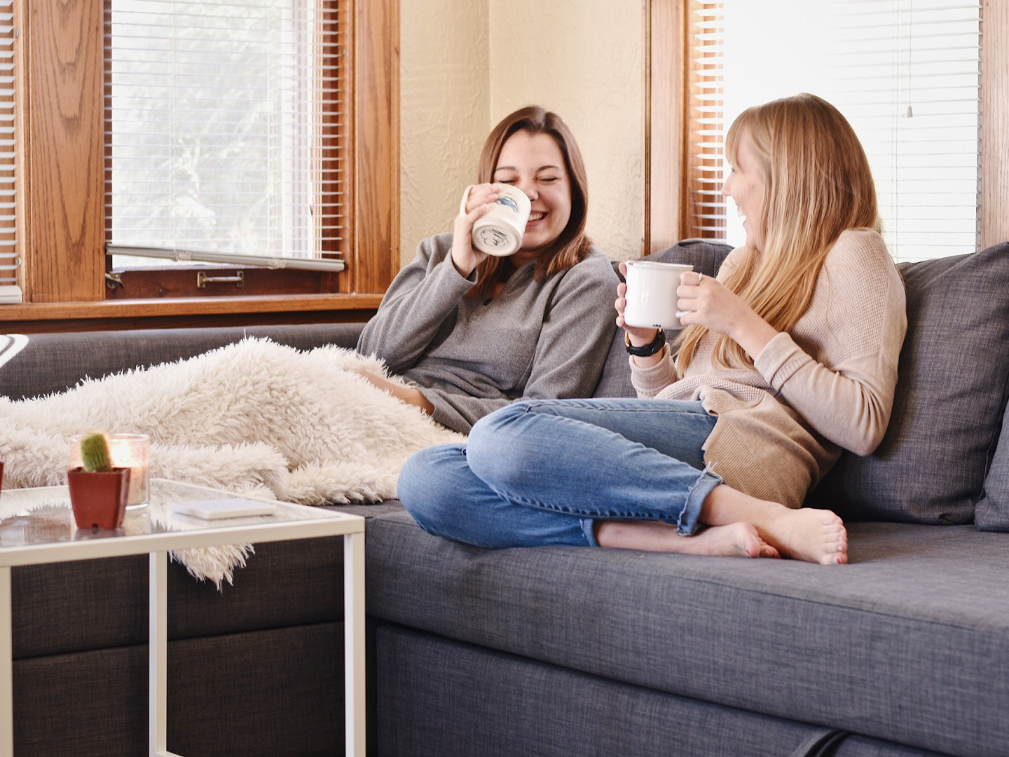 female students on sofa drinking coffee