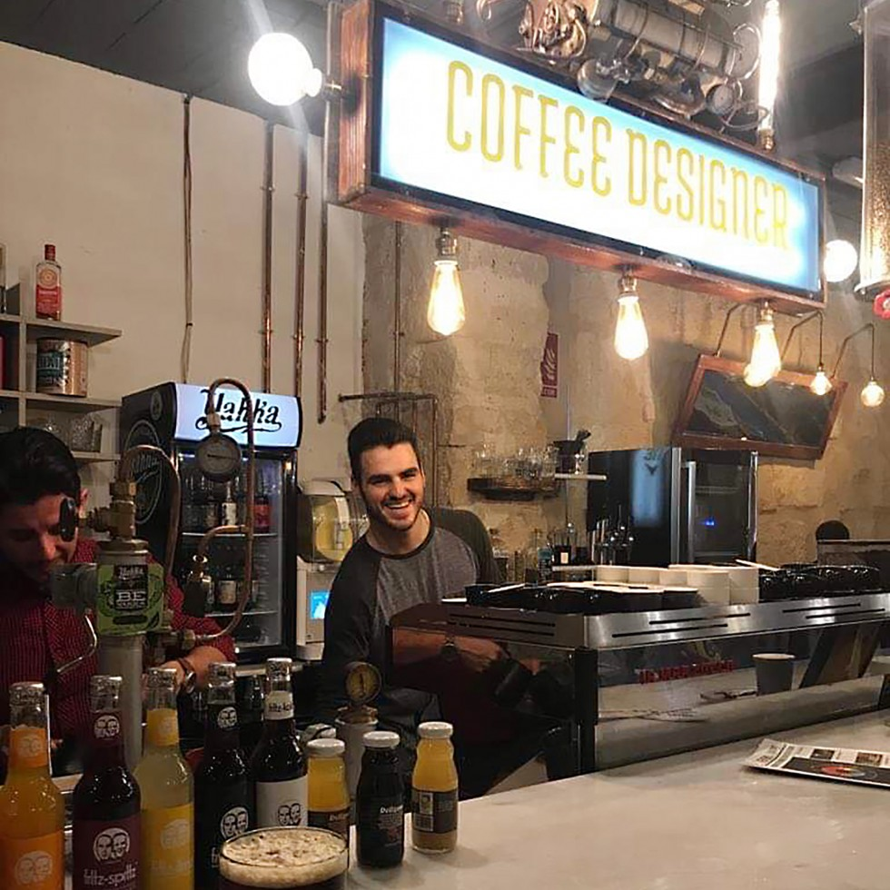 Jackson Booth working at coffee shop behind counter